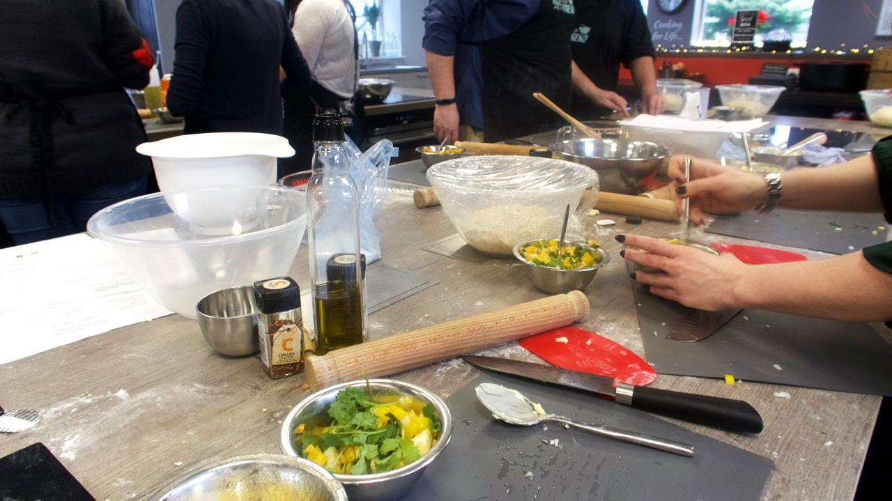 The class underway, kitchen utensils and bowls on a kitchen island